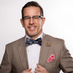head shot of man in suit and bow tie wearing glasses